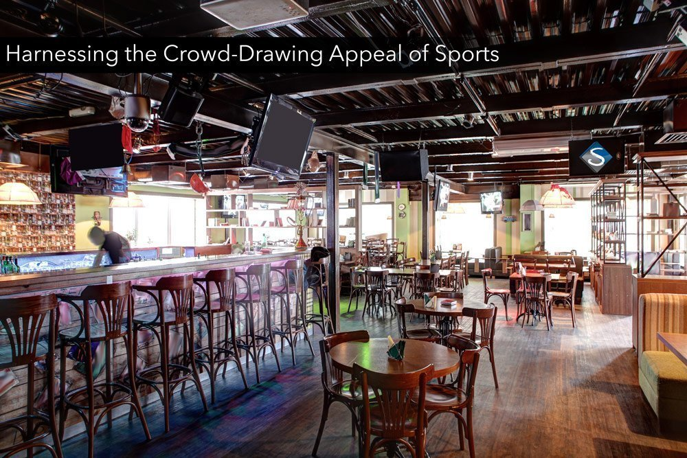 A picture of a sports bar that has great audio visual equipment.